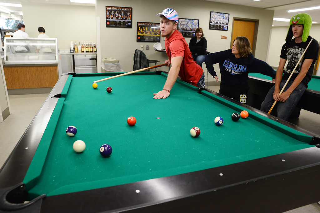 Sheridan College second-year student Curtis Garn, left, stands after making a shot with Lauren Simpson, middle, and Anton Schell looking on during the open house Wednesday in the Thorne-Rider Campus Center at Sheridan College. The Sheridan Press Justin Sheely.