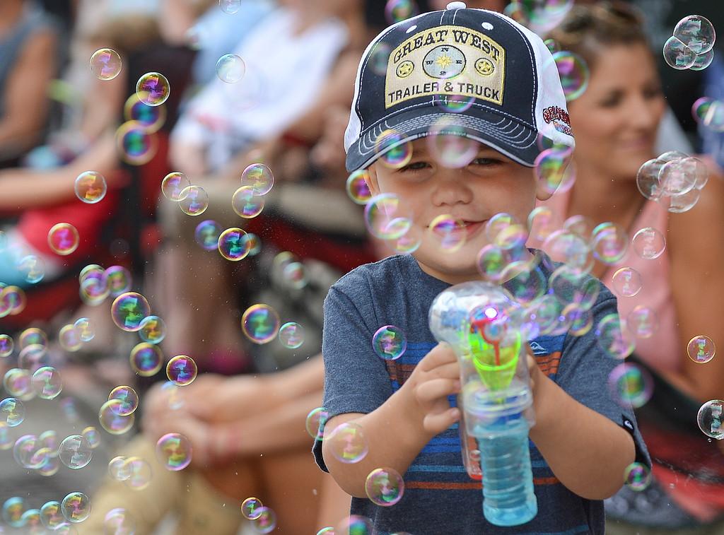 Two-year-old Mac Kay of Arizona sprays bubbles with a bubble gun during the Sheridan WYO Rodeo parade Friday on Main Street. Justin Sheely/The Sheridan Press.