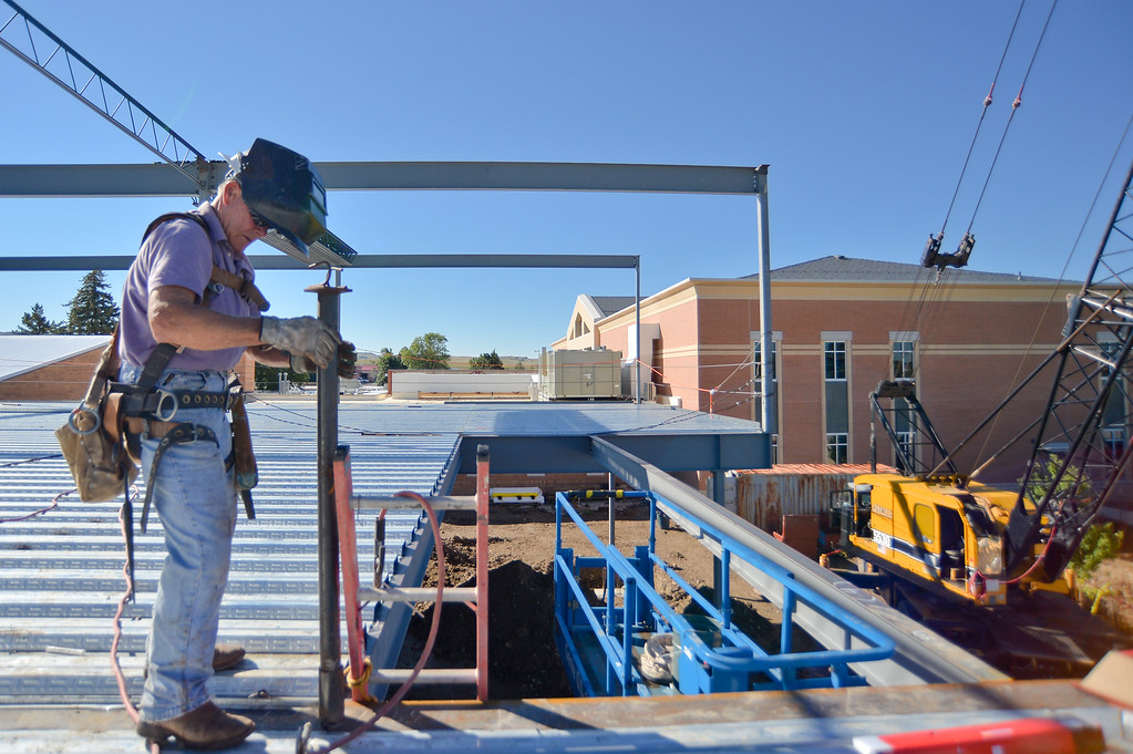 Union Ironworker Everett Phillips installs a temporary handrail on the edge of the second floor of the Whitney Center for the Arts wing construction site Wednesday morning at Sheridan College. The center is part of a 48,000 square-foot remodel of the arts wing that will include a concert hall. The remodel is scheduled to be finished by summer of 2016. Justin Sheely / The Sheridan Press.