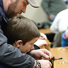Kent Andersen helps Hunter Andersen, 14, with tying a Olive Wooly Bugger during the Trout Unlimited Fly Tying class Saturday at the Fly Shop of the Bighorns. Justin Sheely/The Sheridan Press.