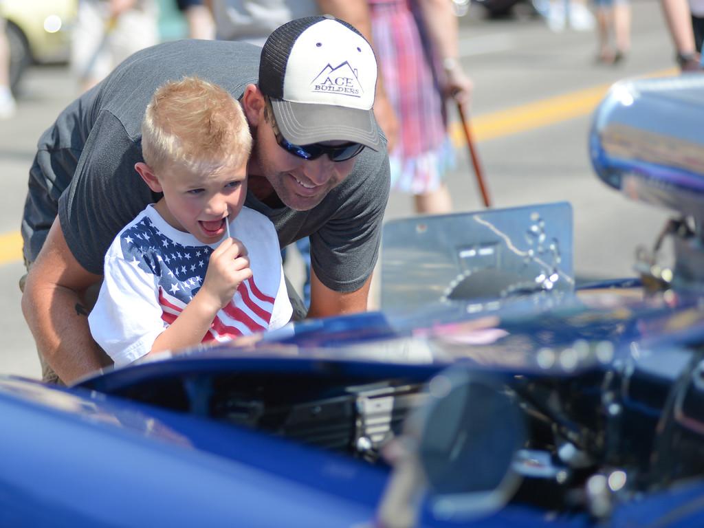 Chris Bernard and his son Nolan Bernard, 5, look at cars during the Karz Rod Run Saturday on Main Street in downtown Sheridan. Justin Sheely/The Sheridan Press.