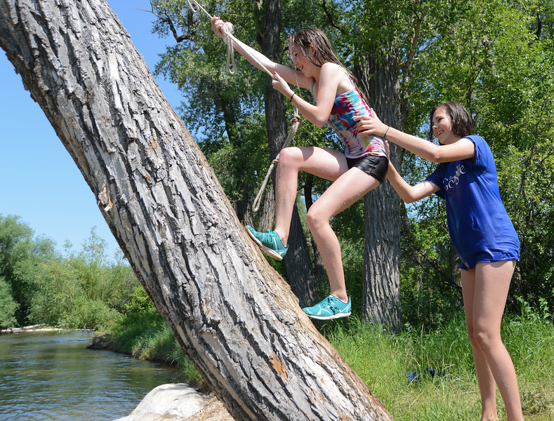 Fourteen-year-old Annie Kerns, left, and Bailee Stewart, 14, climb a tree to swing from a rope swing over the Tongue River Wednesday at the old swimming hole behind Scott Park in Dayton. Temperatures have reached the lower 90s earlier this week. The rest of the week is forecasted to remain hot through Independence Day until cooler air moves in on Sunday. Justin Sheely/The Sheridan Press.