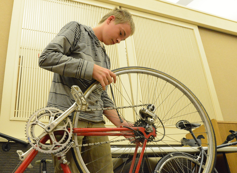 Thirteen-year-old Reece Hendrickson removes a bicycle tire during the free bicycle maintenance class Saturday at the Sheridan County Fulmer Public Library Inner Circle Room. The bicyclists talked about what they use to commute on bikes, how to repair a flat tire, cleaning, and proper sizing. Justin Sheely/The Sheridan Press.