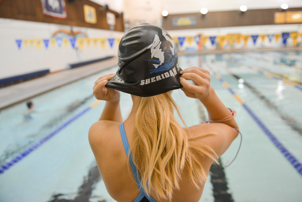 Justin Sheely | The Sheridan Press<br /> A swimmer tucks her hair under a cap during the last day of practice for the Sheridan Sharks swim team Thursday at the pool in the Sheridan Junior High School. The Sharks are heading to the Wyoming Swimming Incorporated state swim meet in Gillette this Friday through Sunday. The Sheridan Sharks swim team will have 21 competitors at state from elementary to high school age.