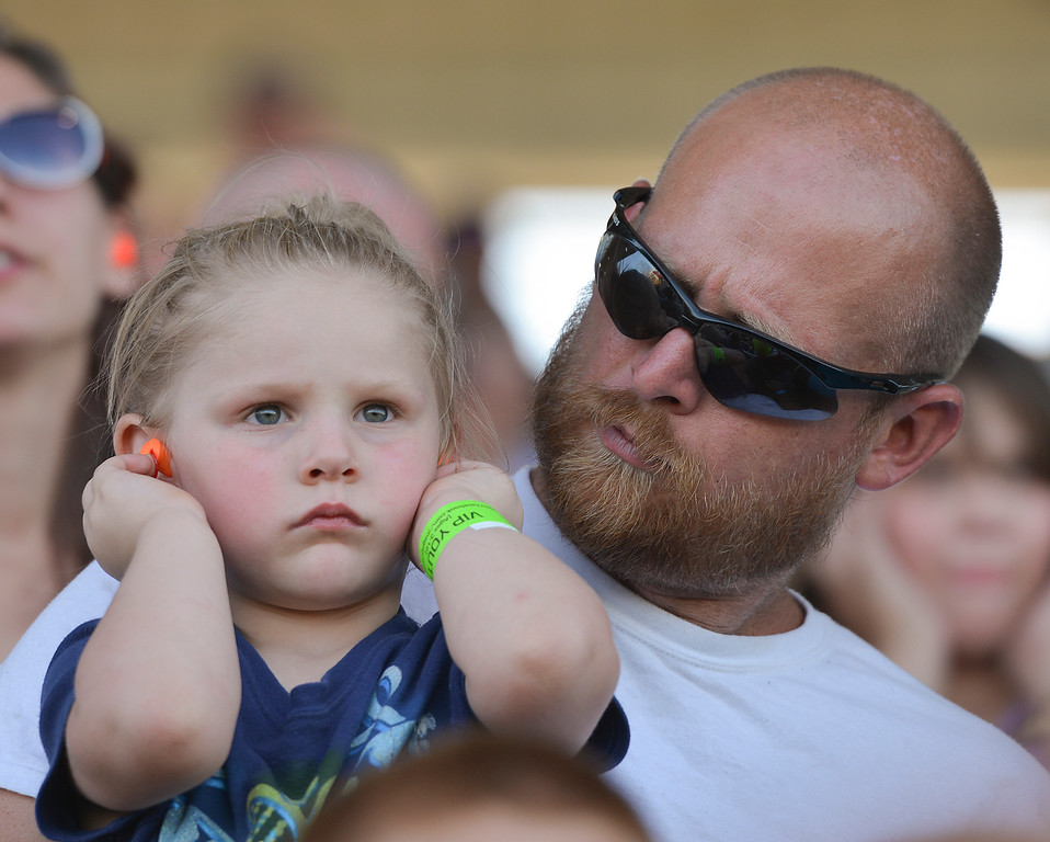 Justin Sheely | The Sheridan Press<br /> Three-year-old Avery Jean tries to block the noise from the monster trucks as she sits with Zachary Christensen during the Mega Promotions Monster Truck show Saturday at the Sheridan County Fairgrounds.
