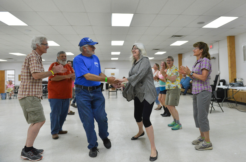 Justin Sheely | The Sheridan Press<br /> Paul Grinvalsky and Kathleen Salvia go down the line for a square dancing workshop during the Bighorn Mountain Music Festival Saturday morning at the Johnson County Fairgrounds in Buffalo. The group was taught appalachian-traditional square dancing, circle dancing and clogging by South Carolina's Pete LaBerge.