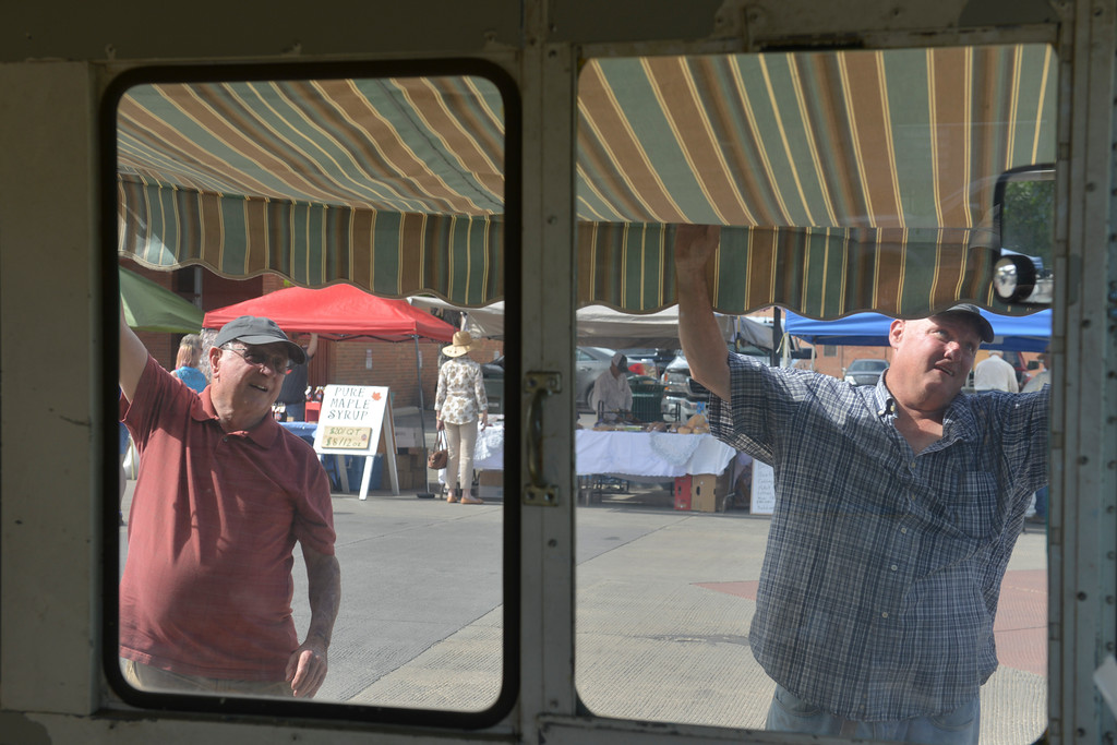 Justin Sheely | The Sheridan Press<br /> Larry small, left, and Chris Small assemble an awning on the side of a repurposed postal truck during setup for the Farmers' Market Thursday at Grinnell Plaza.