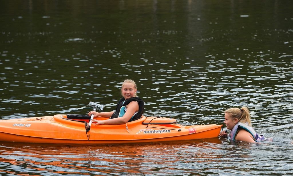 Justin Sheely | The Sheridan Press<br /> Fourth-grader McKinlee Scammon paddles to tow her bigger sister Emma Scammon during an outing by Dayton Community Church youth group Wednesday at Sibley Lake in the Bighorn National Forest.