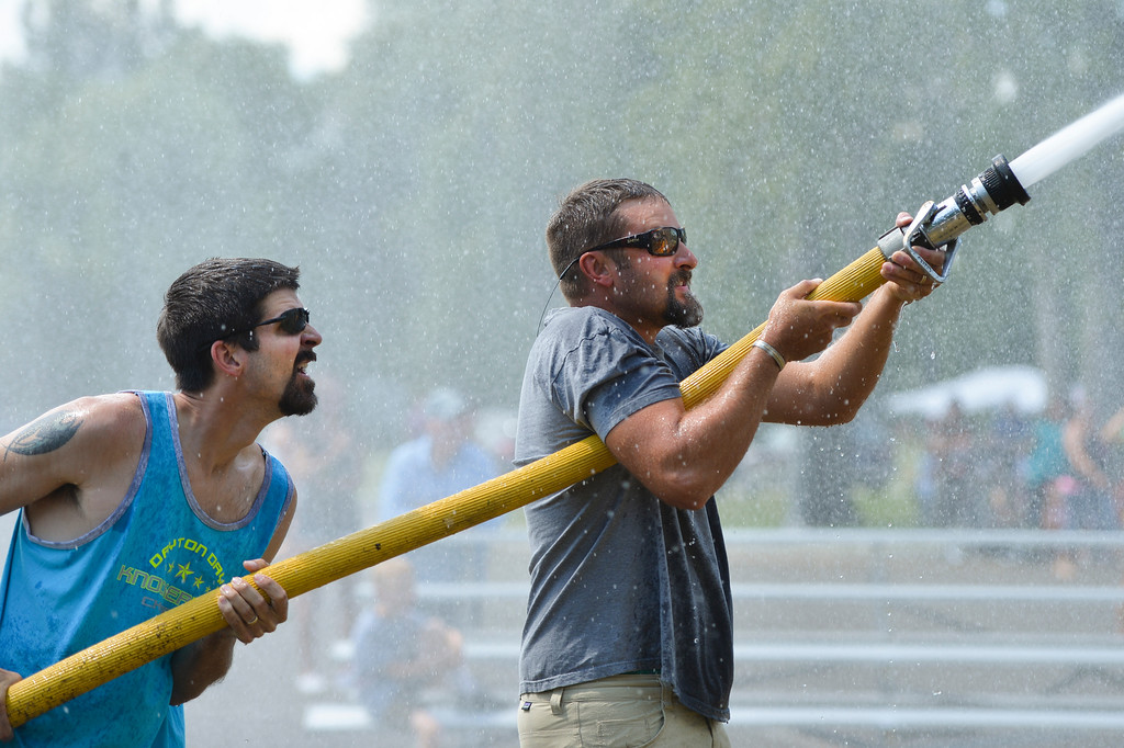 Justin Sheely | The Sheridan Press<br /> Zack Cummins, left, and Matt McMeans aim the water jet at the suspended barrell to push against the other team for the firemen's water fight during the 40th annual Dayton Days Saturday in the town of Dayton. The upper-ninety-degree weather did not stop Tongue River Valley residents from enjoying the day's festivities, including knocker ball, human foosball, duck races and the firemen's water fight.