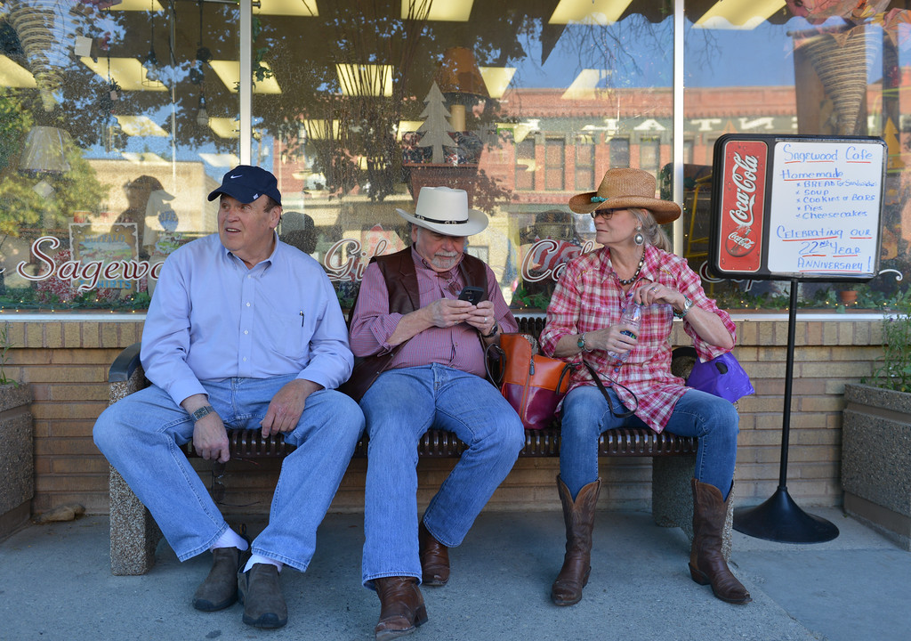 Justin Sheely | The Sheridan Press<br /> Longmire fans, from left, Jack Studenberg of Nebraska, his brother Phil Studenberg, of Oregon, and Jody Daniels, Oregon, sit in the shade as they wait for the Longmire Parade Friday in Buffalo. 2016 marks the 5th year of Longmire Days for the town of Buffalo, which hosted several events involving the cast and members of the crew to meet their fans. Longmire started out on cable television in 2012 and is now a series on Netflix. The show follows the exploits of Sheriff Walt Longmire in fictional Absaroka County, Wyoming. The series is from local author Craig Johnson's books, who based the fictional town in his books on Buffalo, Wyoming.