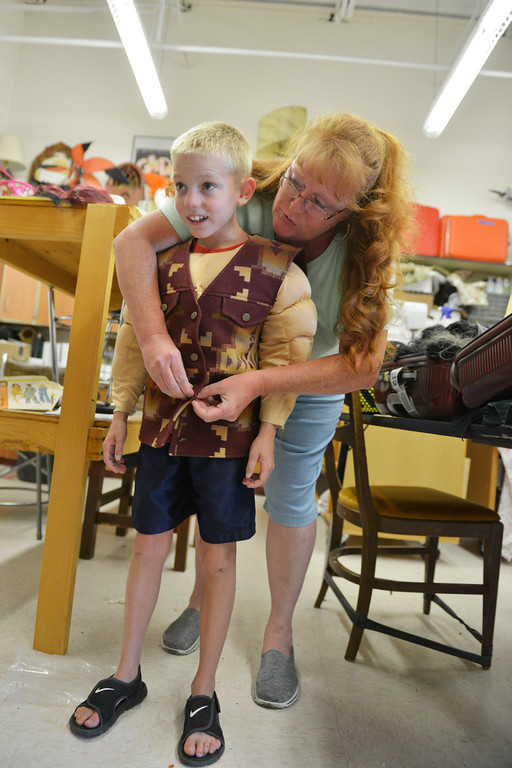 Justin Sheely | The Sheridan Press<br /> Local volunteer Jill Corden puts a costume on nine-year-old Jaxon Sutton, of Buffalo, to play officer Mathias during the Youth Acting Workshop Saturday during Longmire Days. Actor Louanne Stephens – who plays Ruby in Longmire –lead the workshop which is based on an episode of Longmire.