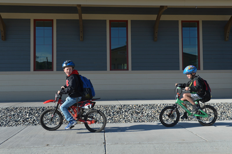 Justin Sheely | The Sheridan Press<br /> Tongue River Elementary students Jordan Garrison, left, and Aiden Smith ride past the mercantile during Bike to School Day Tuesday in Ranchester. Approximately 150 students participated in the bike to school event, which started at the Tongue River Middle school and followed the highway though Ranchester to end at the elementary school. National Bike to School day started in May of 2012 to promote healthy and active lifestyle.