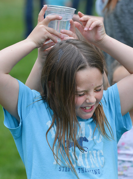Justin Sheely | The Sheridan Press<br /> Second-grader Skye Malli reacts as water spills on her head as the team relays a cup of water for a chain game during the field day event on the last day of school for Sheridan County School District 3 at Arvada-Clearmont Schools Tuesday in Clearmont.