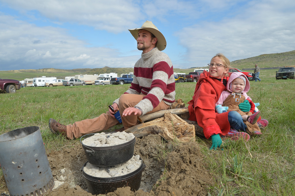 Justin Sheely | The Sheridan Press<br /> From left, Loren Rottinger sits by the dutch oven fire with Katelyn Crump, 9, and Elizabeth Crump during the Ed Green Memorial Rifle Frolic / Black Powder Shoot Friday at the Dannar Ranch north of Sheridan. The weekend-long event is an annual tradition honoring black powder gun enthusiast Ed Green. The events include shooting matches, quail walks, cooking competitions, and egg hunts for the kids. The group celebrate early 1800 s era life by cooking over campfires, dressing in period clothing and shooting black powder rifles.