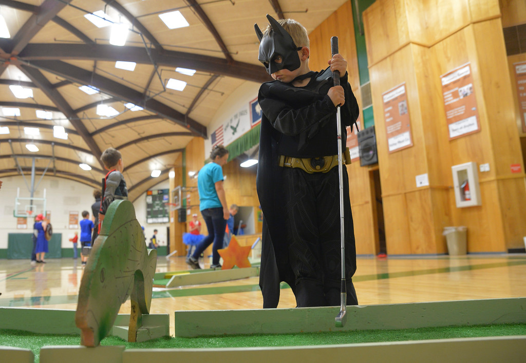 Justin Sheely | The Sheridan Press<br /> Five-year-old Nash Bishop, as the Dark Knight, putts the golf ball during the Mother and Son Superhero Date Night Friday at the Tongue River Valley Community Center in Dayton. The event was a followup to the Daddy and Daughter Dance to provide a fun opportunity for mothers to go on a date with their sons.