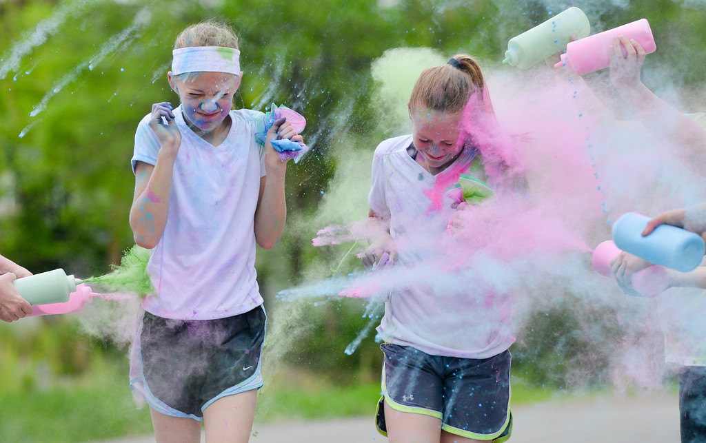 Justin Sheely | The Sheridan Press<br /> Twelve-year-olds Dulce Carroll, left, and Jenna Sweeny get plastered with color during the Sash Dash color run Saturday at Kendrick Park. The event benefits the Miss Wyoming and Miss Wyoming Teen pageant programs.