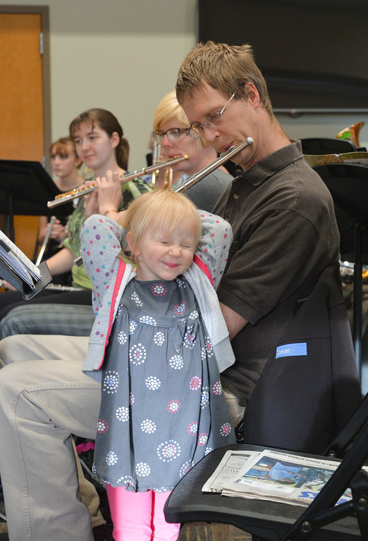 Justin Sheely | The Sheridan Press<br /> Mark Van Houten plays his flute as his three-year-old daughter Katie Van Houten makes a face during the Sheridan College Bands' concert Tuesday at the Thorne-Rider Campus Center. The concert was intended to be held outside at the Whitney Mall but was moved indoors because of windy conditions. This was the last band concert of the school year.