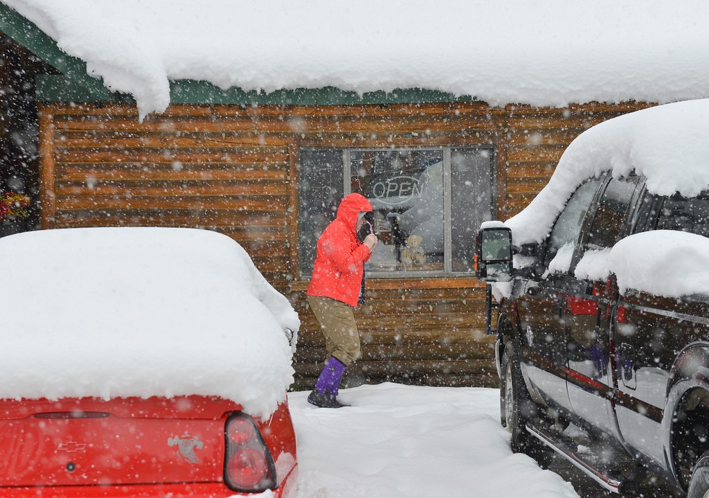 Justin Sheely | The Sheridan Press<br /> A person walks past parked vehicles as snow falls at Bear Lodge Resort Saturday afternoon in the Bighorn National Forest. Heavy snow caused trees to bring down power lines leading to the popular mountain resort. Burgess junction reported up to 6 inches of accumulation as of Saturday afternoon.