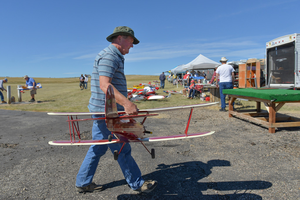 Justin Sheely | The Sheridan Press<br /> Bob Abelman of Billings, Montana, carries his 1930s-era Waco biplane model to the table to empty out the fuel during the annual Cowboys Fly-in Saturday at the Sheridan County Sportsman Gun Club.