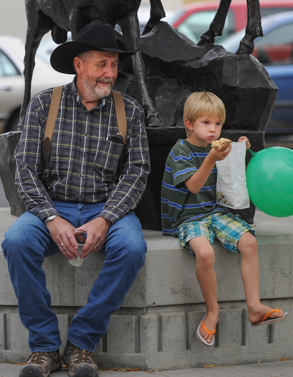 Justin Sheely | The Sheridan Press<br /> Bill Schilling, left, watches as Nathan Anderson, 5, eats a snack during the last Farmers Market of the season Thursday on Grinnell Plaza.