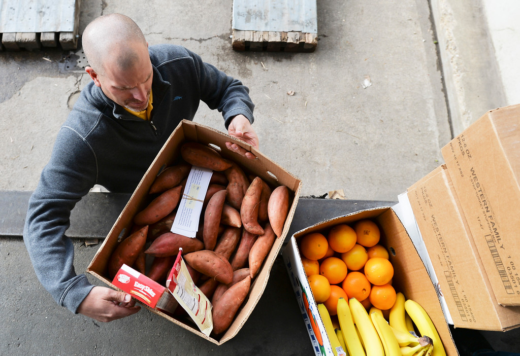 Justin Sheely | The Sheridan Press<br /> Food Group volunteer Josh Gardner picks up a box of fruit and vegetables Monday morning for Big Horn Schools for Thanksgiving Day distribution.