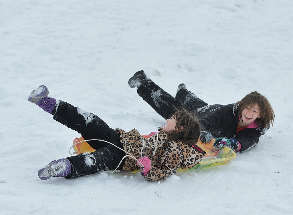 Justin Sheely | The Sheridan Press<br /> Eight-year-old Azzy Brown, left, holds on to the rope as her sister Zia Brown, 11, hangs onto the sled as they go down Linden Hill Saturday in Sheridan.