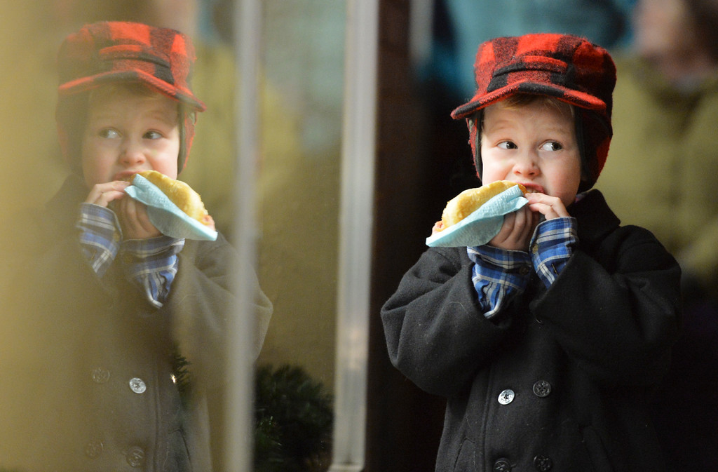 Justin Sheely | The Sheridan Press<br /> Four-year-old Sloan Skarlupka digs into his hotdog during the annual Christmas Stroll Friday on Main Street. The event is to encourage the community to shop local and and provides fun activities for children, including wagon rides and pictures with Santa.