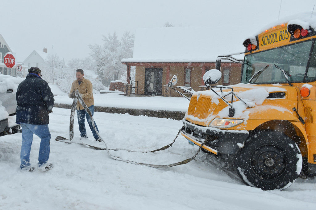 Justin Sheely | The Sheridan Press<br /> Bus driver Richard Dankert, left, carries a tow rope over to a truck after his bus gets stuck on a hill on E Perkins and S Main Street Thursday morning. The bus got stuck going uphill on the slick road. Students were transferred to another bus – no one was injured. Some areas in Sheridan received up to 8 inches of snow early Thursday morning, creating hazardous driving conditions.