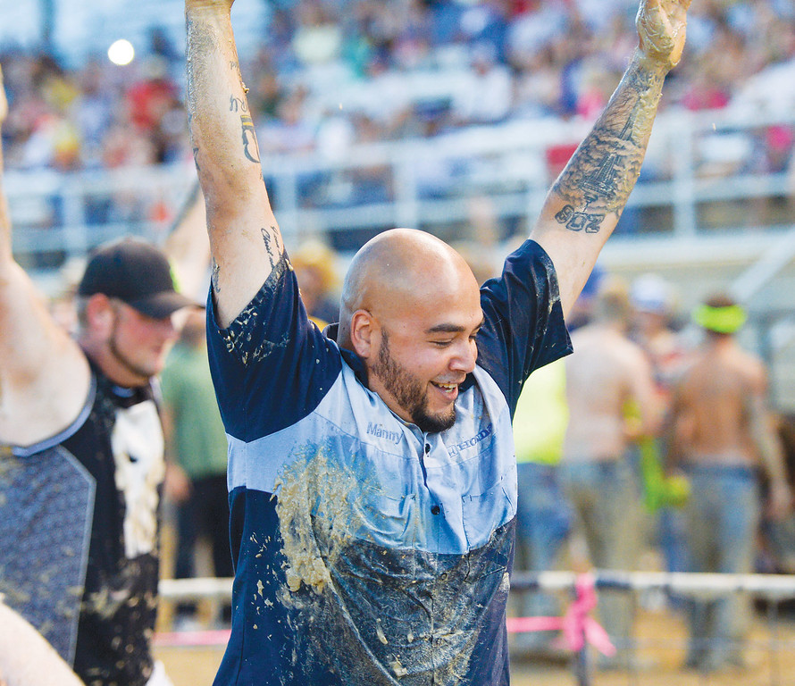 Mike Dunn | The Sheridan Press.<br /> Manny Swamy raises his hands after his team the Honda Hogs finished first in the mens pig wrestling with a time of 13.86 seconds. Several spectators attended the Sheridan County Fair Pig Wrestling event Saturday at the Sheridan County Fairgrounds Arena.