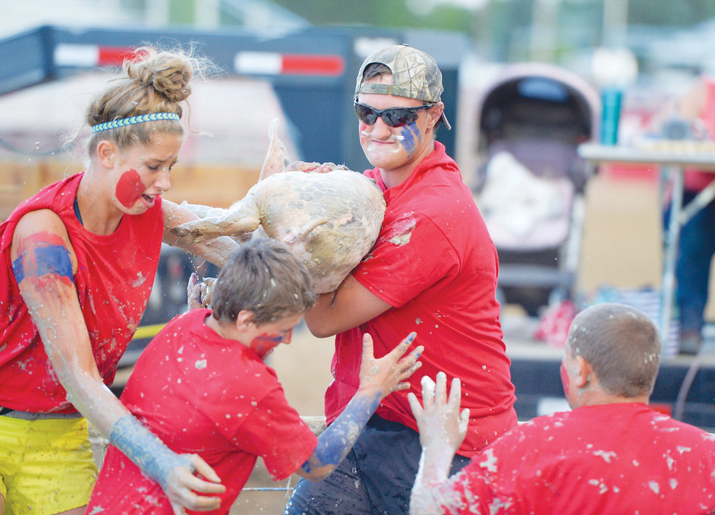 Mike Dunn | The Sheridan Press<br /> Pictured from left, Kylie Sorenson, Bratton Ankney, Wyatt Ankney and Thomas Sorenson scramble to put a pig into the bucket for the Sheridan County Fair pig wrestling contest Saturday at the Sheridan County Fairgrounds arena.