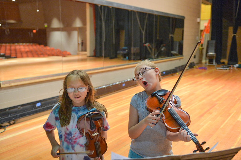 Justin Sheely | The Sheridan Press<br /> Eleven-year-old Victoria Smith, left, and Bri Doke, 9, practice together during the Summer Strings program Thursday at Sheridan High School. The program is lead by Razmick Sarkissian, SHS director of orchestras, for elementary students. The week long program ends Friday at noon with a concert for the youth's family and the general public at the Sue Henry auditorium.
