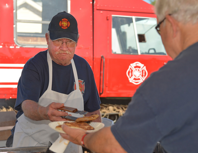 Justin Sheely | The Sheridan Press<br /> Firefighter Dennis Loomis serves sausage during the annual pancake breakfast Saturday at the Big Horn fire station. The volunteer fire department served breakfast for the community and held tours of the fire engines.
