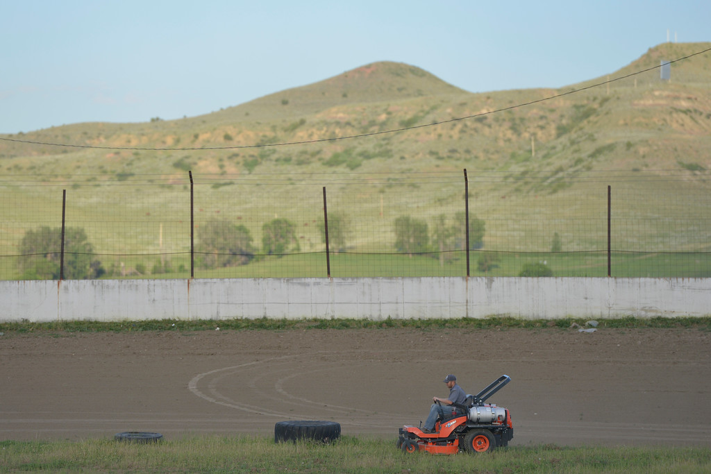 Justin Sheely | The Sheridan Press<br /> A volunteer runs a riding lawnmower over the pit of the race track during a clean up day by the Sheridan Motorsports Association Thursday evening at Sheridan Speedway. Dozens of volunteers came to clean up trash, cut weeds and make improvements to the dirt track and facilities after the speedway closed earlier this month. The association plans to open up the track for its first event of the year on Sunday, June 26 at 5 p.m. Tickets are $12 for adults, $8 for seniors and students. Free admission for children under 12.