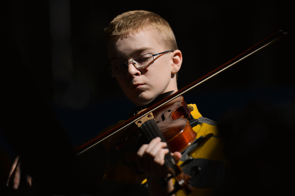 Justin Sheely | The Sheridan Press<br /> A beam of sunlight isolates Carter Steidley from the darker room as he practices on the violin during the Summer Strings program las June at Sheridan High School.