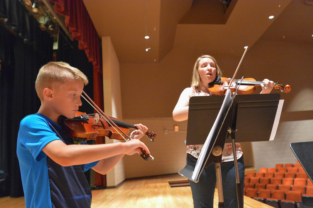 Justin Sheely | The Sheridan Press<br /> Nine-year-old Cameron Steidley practices on his violin with elementary orchestra teacher Erin Cummings during the Summer Strings program Thursday at Sheridan High School. The program is lead by Razmick Sarkissian, SHS director of orchestras, for elementary students. The week long program ends Friday at noon with a concert for the youth's family and the general public at the Sue Henry auditorium.