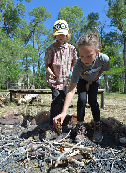 Justin Sheely | The Sheridan Press<br /> Eight-year-old Cierra Maher, left, and Sydney Herrigel, 9, place pine cones to start a campfire during the Girl Scouts' Camp Rowena Wednesday at the Poulson Griffith youth camp on Big Goose Road. The day camp is designed to teach camp skills and safety to brownies and daisy scout girls. Camp Rowena has been held every year at Poulson Griffith since the 1960s.