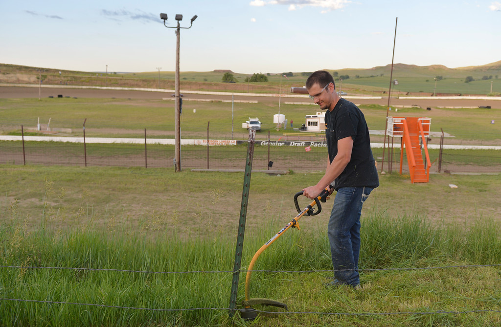 Justin Sheely | The Sheridan Press<br /> Justin Elmer, president of the Sheridan Motorsports Association, runs a weedeater during a clean up day by the Sheridan Motorsports Association Thursday evening at Sheridan Speedway. Dozens of volunteers came to clean up trash, cut weeds and make improvements to the dirt track and facilities after the speedway closed earlier this month. The association plans to open up the track for its first event of the year on Sunday, June 26 at 5 p.m. Tickets are $12 for adults, $8 for seniors and students. Free admission for children under 12.