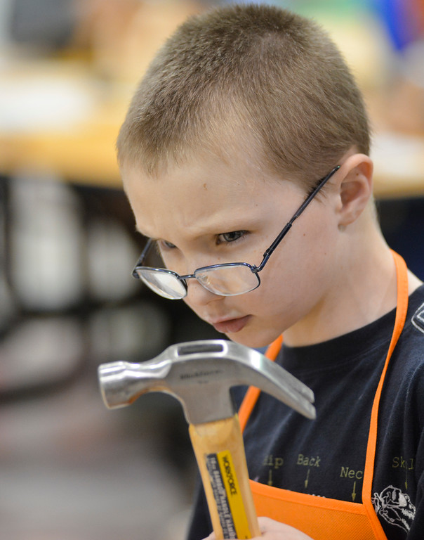 Justin Sheely | The Sheridan Press<br /> Kindergartener Heath Dobrenz readies a hammer during the annual Home Depot birdhouse building Wednesday at Sagebrush Elementary School. This is the eighth year Sheridan's Home Depot store donated wood birdhouse kits for more than 60 kindergarten students to build with their dads. Each kindergartener built a birdhouse with their father, or other significant male figure, decorated it and took it home. The Home Depot in Sheridan offers free workshops for youth every first Saturday of the month. Details can be found in-store.