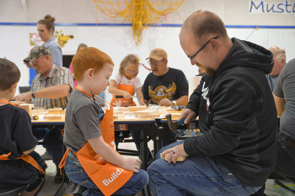 Justin Sheely | The Sheridan Press<br /> Kindergartener Elam Hamby watches as Jason Hamby pulls a nail during the annual Home Depot birdhouse building Wednesday at Sagebrush Elementary School. This is the eighth year Sheridan's Home Depot store donated wood birdhouse kits for more than 60 kindergarten students to build with their dads. Each kindergartener built a birdhouse with their father, or other significant male figure, decorated it and took it home. The Home Depot in Sheridan offers free workshops for youth every first Saturday of the month. Details can be found in-store.