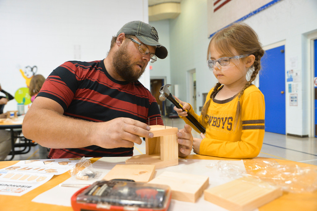 Justin Sheely | The Sheridan Press<br /> Bryon Whisler helps his daughter Kaylee Whisler during the annual Home Depot birdhouse building Wednesday at Sagebrush Elementary School. This is the eighth year Sheridan's Home Depot store donated wood birdhouse kits for more than 60 kindergarten students to build with their dads. Each kindergartener built a birdhouse with their father, or other significant male figure, decorated it and took it home. The Home Depot in Sheridan offers free workshops for youth every first Saturday of the month. Details can be found in-store.