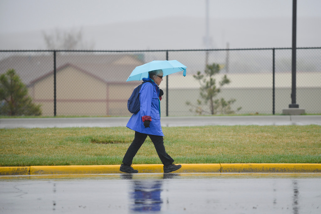 Justin Sheely | The Sheridan Press<br /> A woman walk under soggy weather Tuesday morning on S. Sheridan Avenue. The forecast for the rest of the week is sunny and warm. Friday will see a high of 81-degrees according to the National Weather Service.