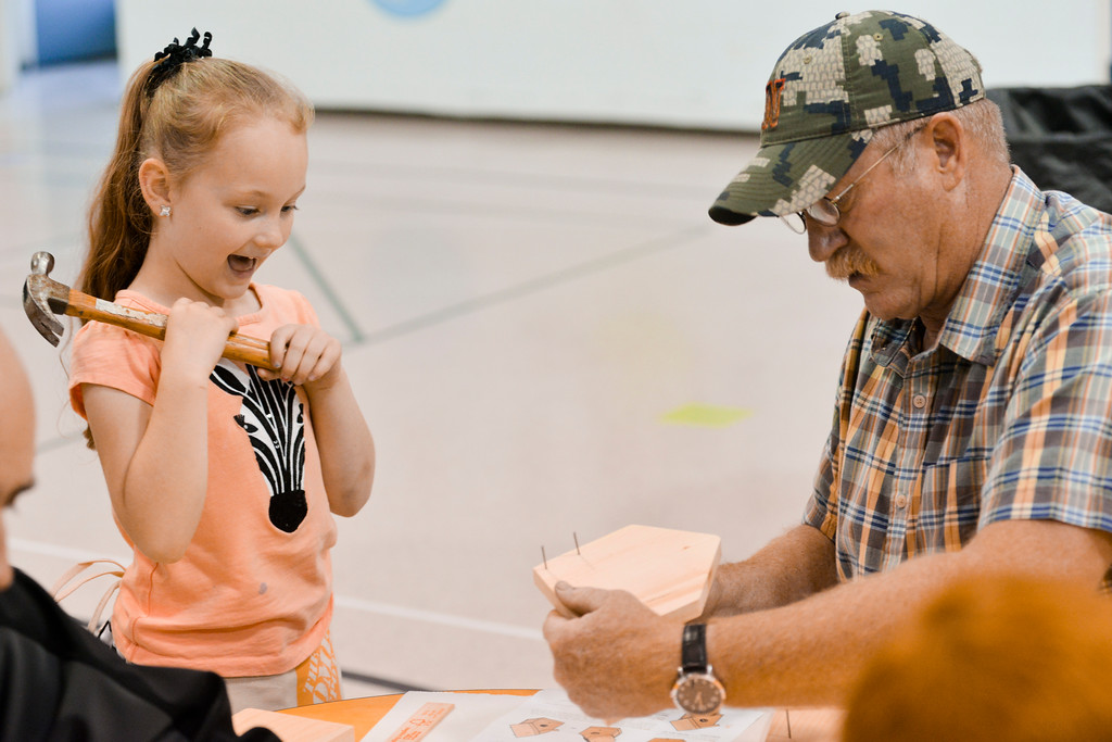 Justin Sheely | The Sheridan Press<br /> Kindergartener Allison Doke waits with hammer ready as her grandfather Dan Doke sets up the pieces during the annual Home Depot birdhouse building Wednesday at Sagebrush Elementary School. This is the eighth year Sheridan's Home Depot store donated wood birdhouse kits for more than 60 kindergarten students to build with their dads. Each kindergartener built a birdhouse with their father, or other significant male figure, decorated it and took it home. The Home Depot in Sheridan offers free workshops for youth every first Saturday of the month. Details can be found in-store.