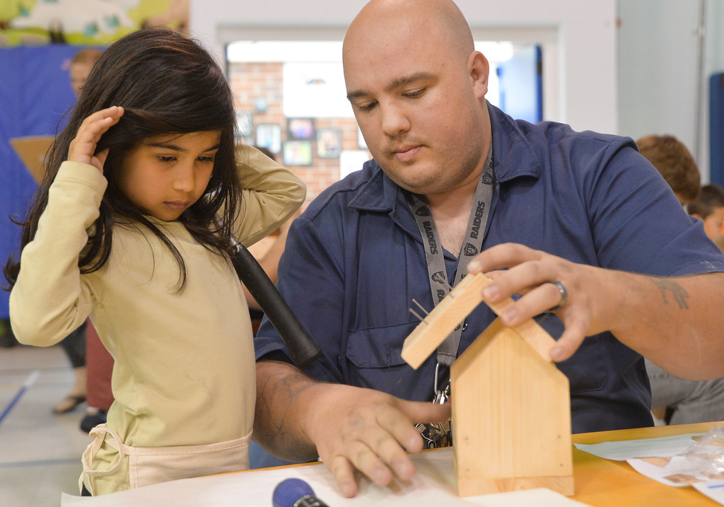 Justin Sheely | The Sheridan Press<br /> Kindergartener Ella Dossin pushes back her hair as Walter Blackburn puts pieces in place during the annual Home Depot birdhouse building Wednesday at Sagebrush Elementary School. This is the eighth year Sheridan's Home Depot store donated wood birdhouse kits for more than 60 kindergarten students to build with their dads. Each kindergartener built a birdhouse with their father, or other significant male figure, decorated it and took it home. The Home Depot in Sheridan offers free workshops for youth every first Saturday of the month. Details can be found in-store.