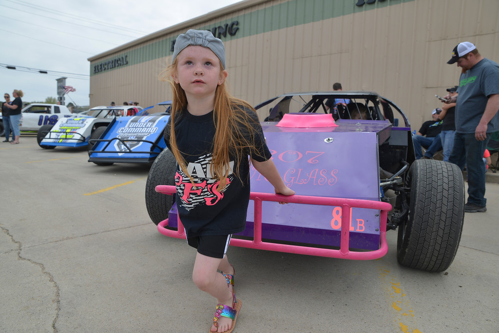 Justin Sheely | The Sheridan Press<br /> Seven-year-old Mia Baxter pulls at her dad's A-Mod race car during the racing car show Saturday at Bloedorn Lumber. Racers who are competing this summer at Cloud Peak Raceway, formerly Sheridan Speedway, were invited to show their race cars to the public Saturday.
