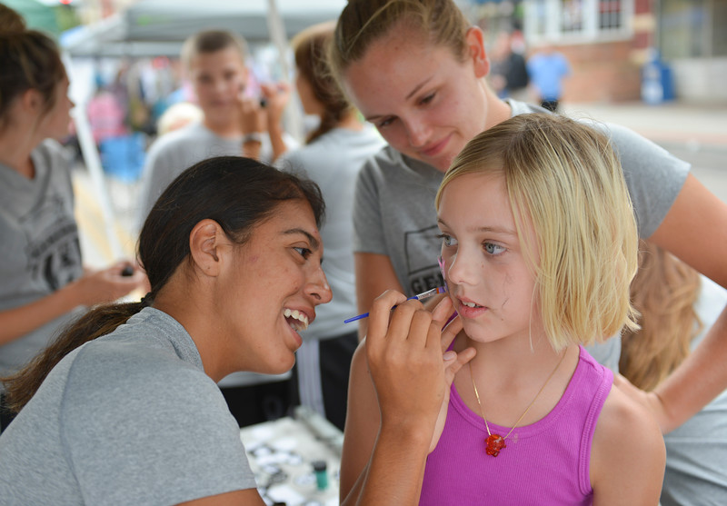 Justin Sheely | The Sheridan Press<br /> Eight-year-old Heather Cossel gets a butterfly painted on by Lady Generals soccer player Ana Sanchez of Cheyenne during the Third Thursday on Main Street. The Sheridan College women's soccer first home game is September 3 at 2 p.m.