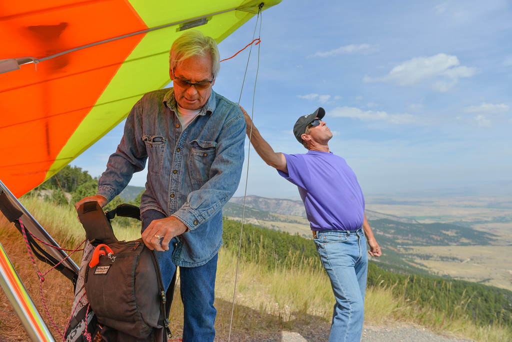 Justin Sheely | The Sheridan Press<br /> Local flyer Johan Nield suits up as Paul Lundquist holds down the hang glider during the hang gliders fly-in Saturday at sand turn west of Dayton. Hang gliders from across the nation come to the Bighorn Mountains every Memorial Day and Labor Day weekends to take advantage of the ideal flying condition that the eastern slopes have to offer.