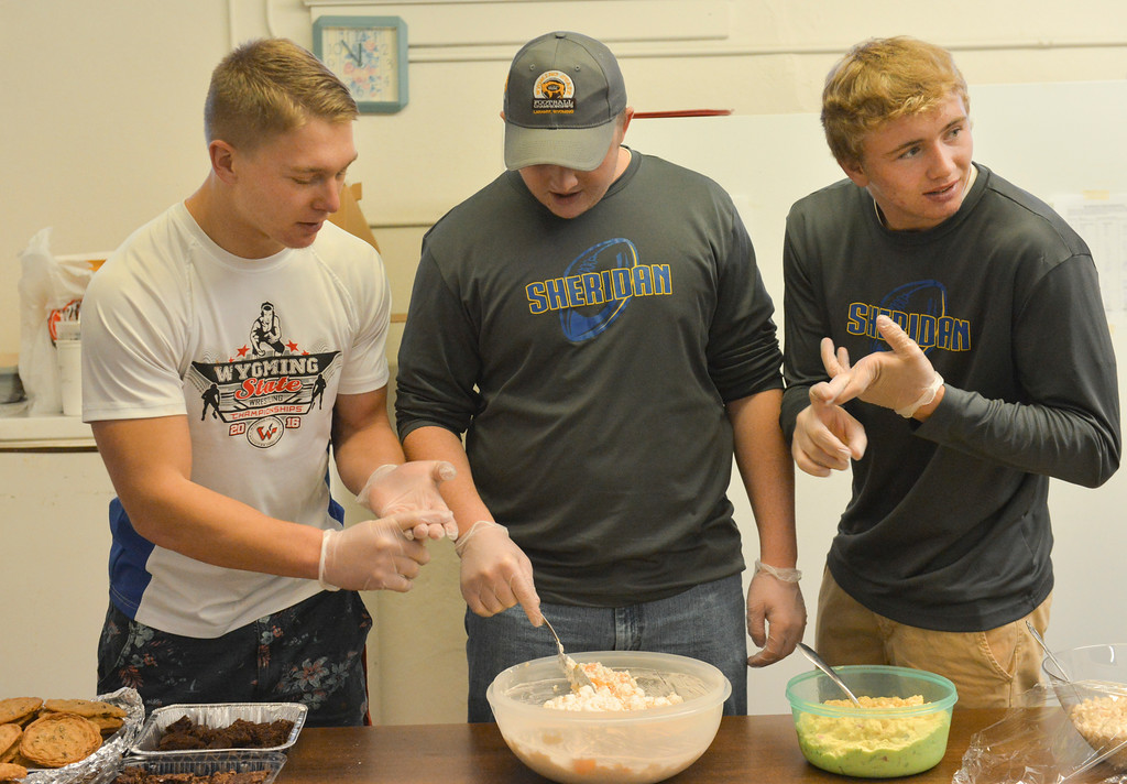 Justin Sheely | The Sheridan Press<br /> Sheridan High School football team members, from left, Jacek Aksamit, Andrew Boint and Hayden Hastings get ready to serve in the community soup kitchen Friday at First Congregational Church on Works Street.