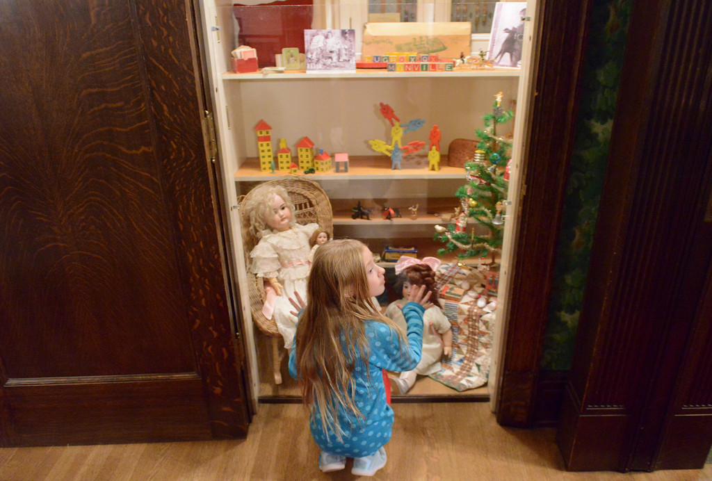 Justin Sheely | The Sheridan Press<br /> Nine-year-old Mercedes Kwallek looks at a closet filled with toys during the Holiday Open House at the Trail End State Historic Site Friday evening. Festivities at site, also called Kendrick Mansion, included guest performances, figgy pudding and a visit from Father Christmas.
