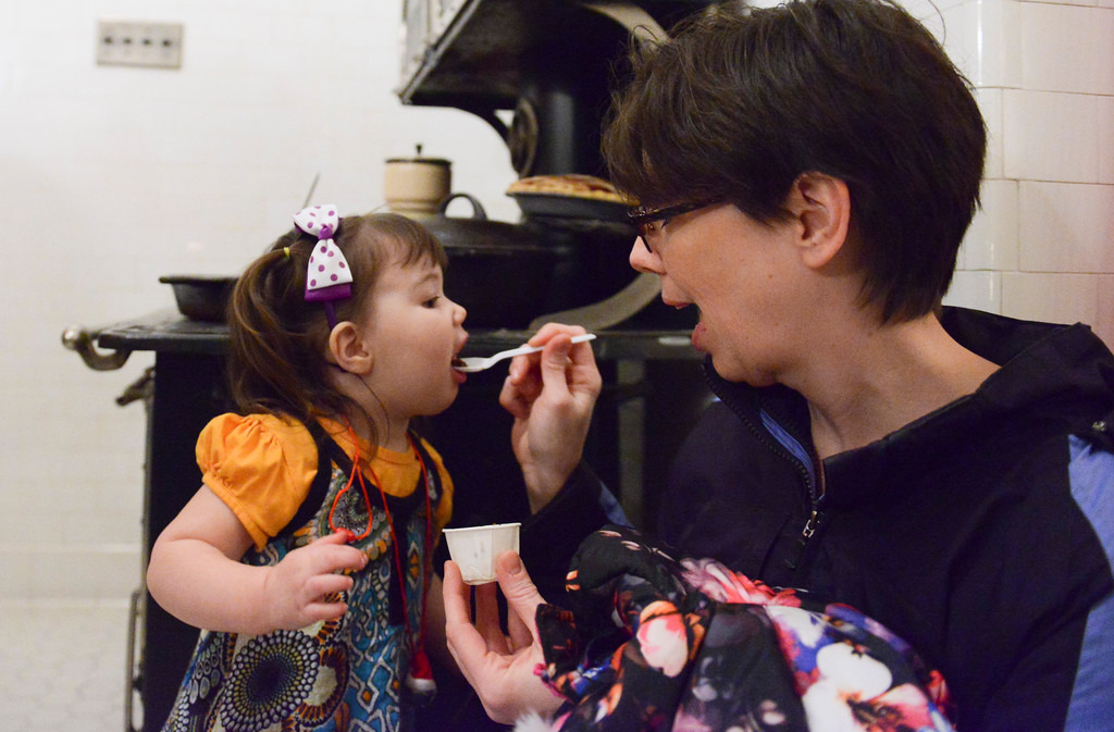 Justin Sheely | The Sheridan Press<br /> Jodi Shell spoons some figgy pudding for her daughter Martha Shell, 2, during the Holiday Open House at the Trail End State Historic Site Friday evening. Festivities at site, also called Kendrick Mansion, included guest performances, figgy pudding and a visit from Father Christmas.