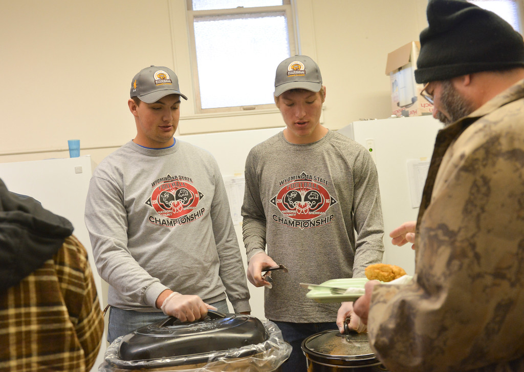 Justin Sheely | The Sheridan Press<br /> Sheridan High School football team members Dillon Shaw, left, and Tyler Holloway serve a guest in the community soup kitchen Friday at First Congregational Church on Works Street.
